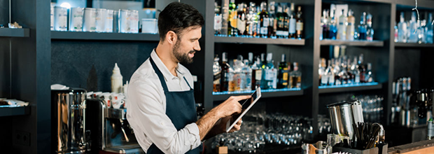 barman-standing-in-apron-and-typing-on-digital- tablet